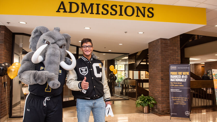 Don the Mastodon and a student give a thumbs up outside of the admissions office.