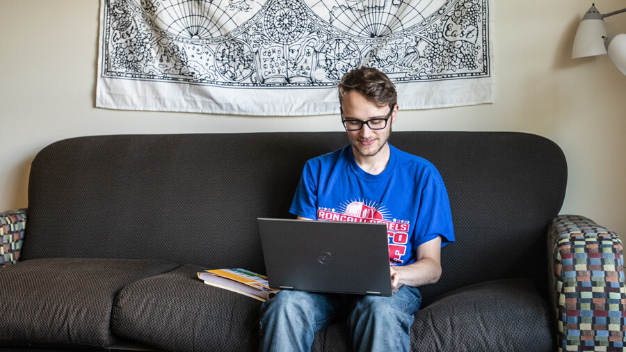 A student uses their laptop while sitting on their couch.